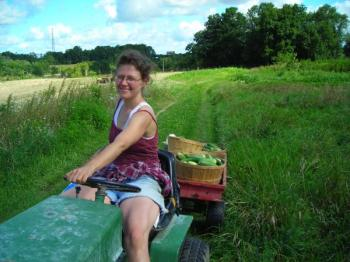 Amy Newday, organizer of the seminar, drives across farm with a bushel of fresh cucumbers.