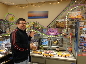Cooper Poses in his office with his roller coaster. Photo by Elaine Ezekiel